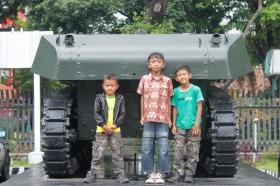anak-anak bergaya di belakang tank