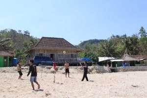 Pengunjung melakukan olah raga voli pantai dengan bola plastik