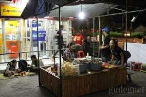 Mbak Sasha sedang melayani pembeli di warungnya jelang tengah malam